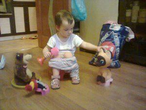 Ребёнок на горшке приучает к горшку свои игрушки