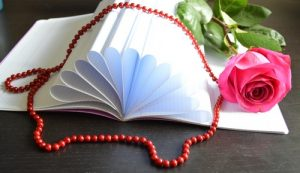Красная роза, красные бусы, чернила, перо и тетрадь