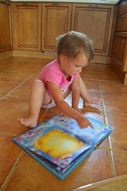 Малышка и книга - иллюстрация к статье о том, как помочь ребёнку запоминать стихи