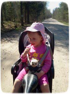 Девочка с леденцом на палочке в велокресле