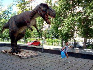 Девочка с пакетом убегает от динозавра